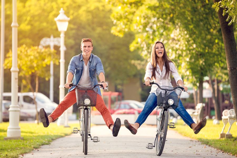 フリー写真 両足を上げて自転車に乗るカップル