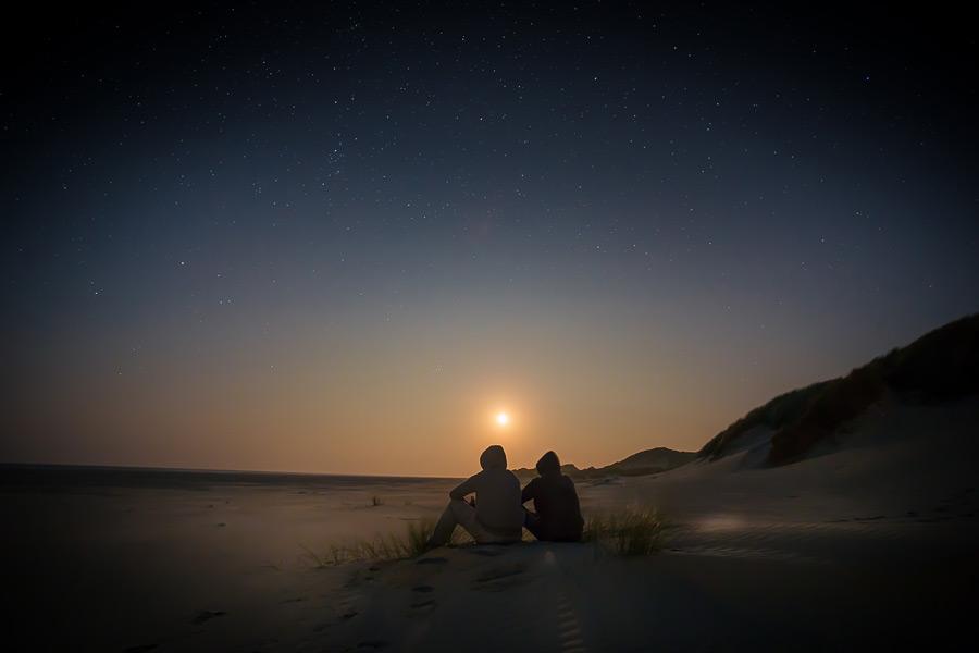 フリー写真 夕暮れのテルスヘリング島のビーチに座る二人の人物