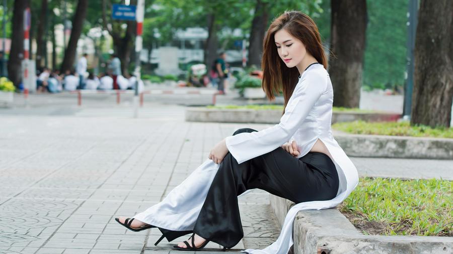 フリー写真 アオザイ姿で座っているベトナム人女性