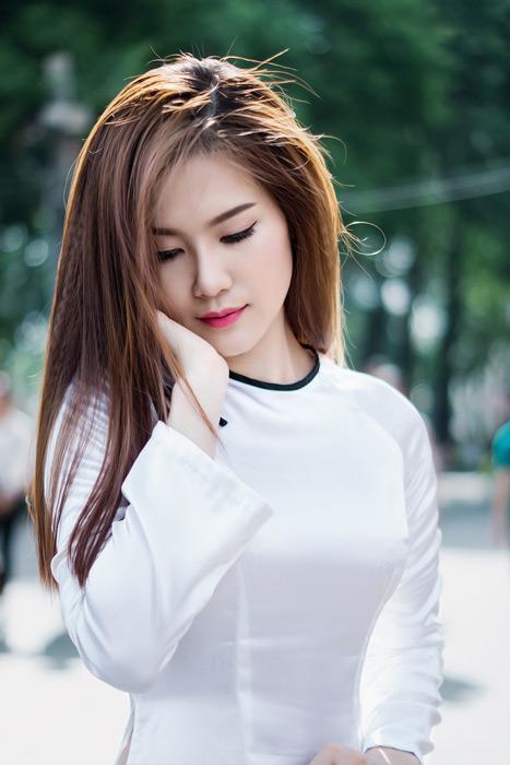 フリー写真 アオザイ姿で頬に手を当てるベトナム人女性