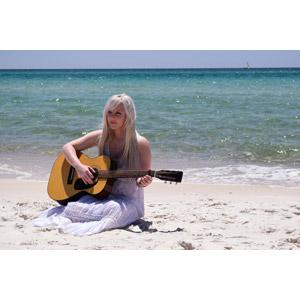 フリー写真, 人物, 女性, 外国人女性, 女性(00114), アメリカ人, 金髪(ブロンド), 音楽, 楽器, 弦楽器, ギター, アコースティックギター, 演奏する, 海, ビーチ(砂浜), 座る(地面)