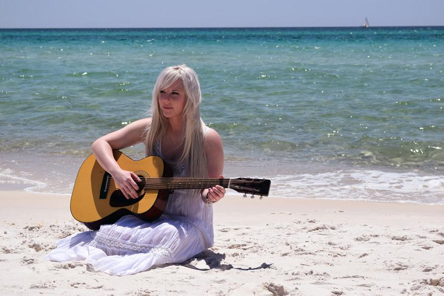 フリー写真 砂浜でギターを弾く外国人女性