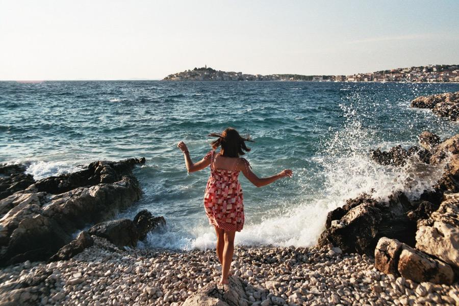 フリー写真 海岸の石の上に立つ女性の後ろ姿