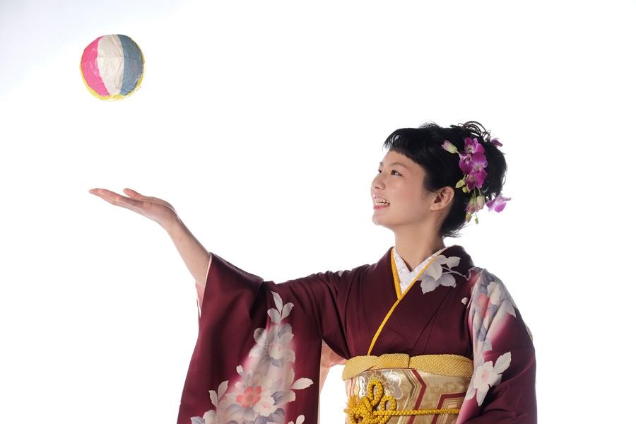 フリー写真 振り袖姿で紙風船で遊ぶ女性