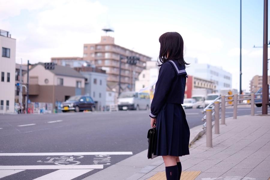 フリー写真 セーラー服姿で信号待ちの女子高生