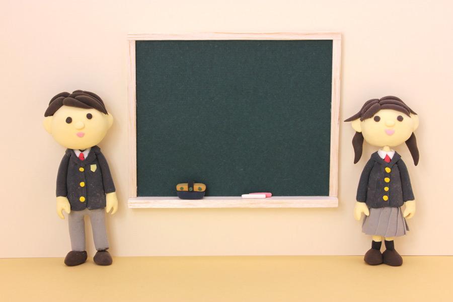 フリー写真 黒板と男子学生と女子学生の人形
