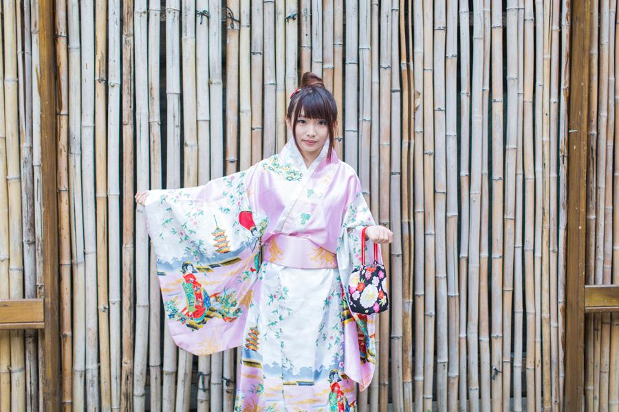 フリー写真 着物姿で竹の壁の前に立つ女性