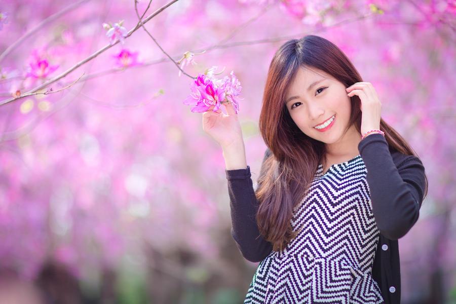 フリー写真 ピンク色の木花と髪をかき上げる女性
