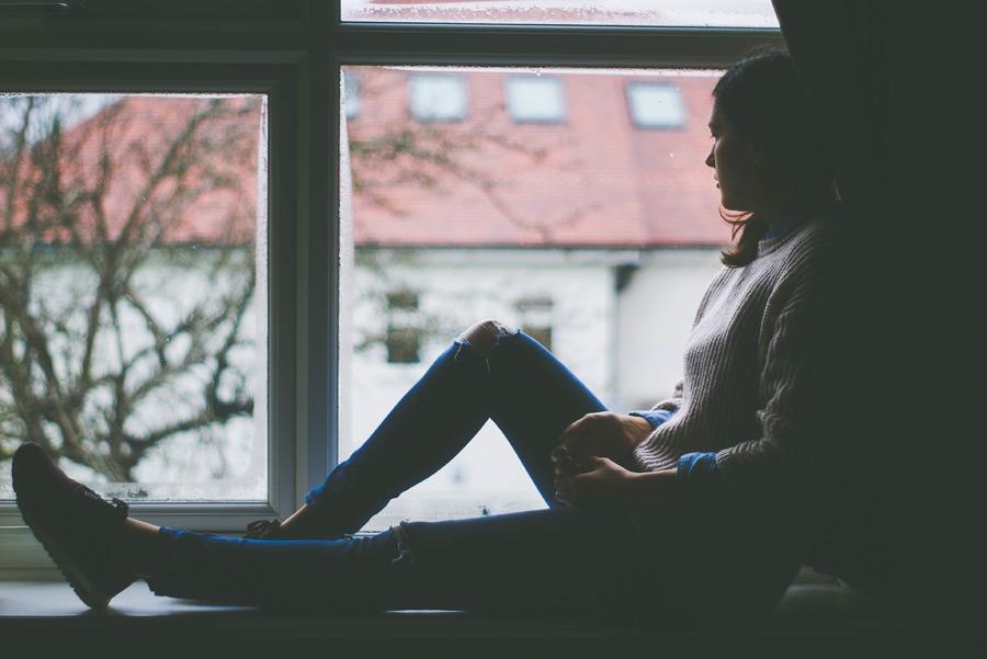 フリー写真 出窓に腰掛けて外を見ている外国人女性