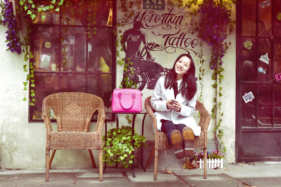 フリー写真 足を伸ばして戸外の椅子に座る女性