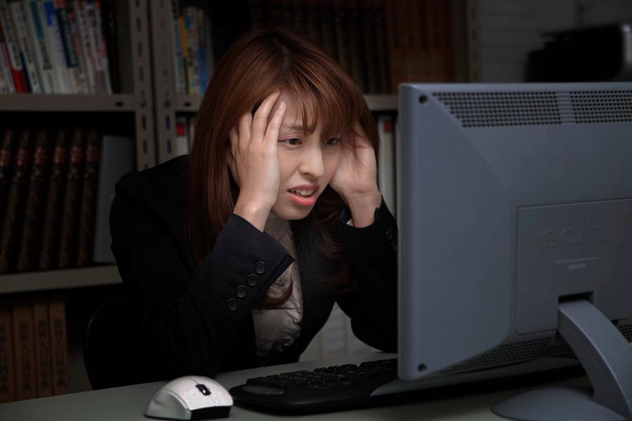 フリー写真 パソコンの前で頭を抱える女性社員