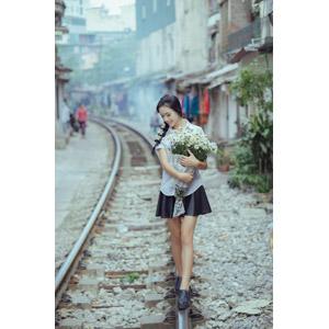 フリー写真, 人物, 少女, アジアの少女, 少女(00118), ベトナム人, 三つ編み, 人と花, 花束, 白色の花, 学生服, 学生(生徒), 人と風景, 線路(鉄道), 俯く(下を向く)