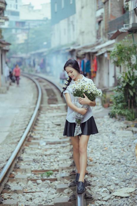 フリー写真 花束を抱えて線路の上を歩く女子学生