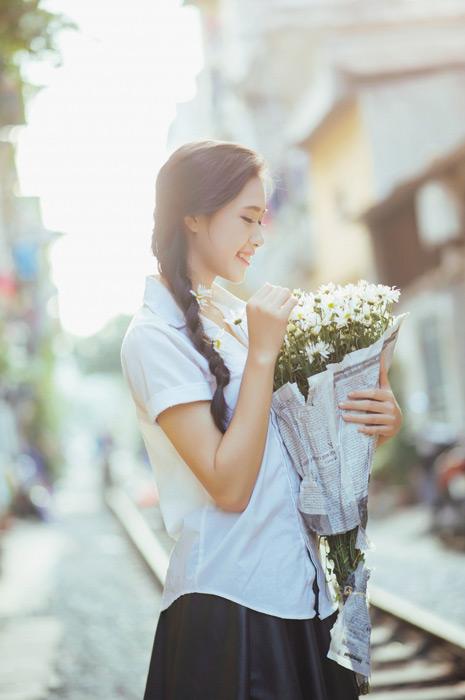 フリー写真 学生服姿で花束を抱える女子学生