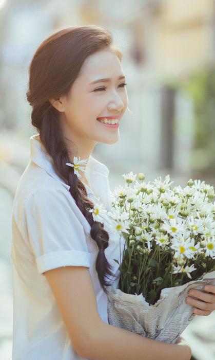 フリー写真 笑顔で花束を抱えている女子学生