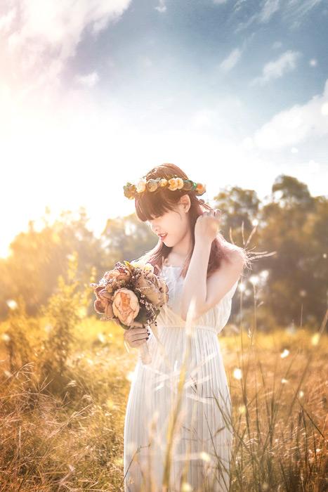 フリー写真 草むらで花束を持つベトナムの女性