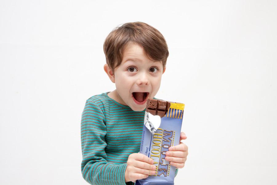 フリー写真 口を開けて板チョコを食べる男の子
