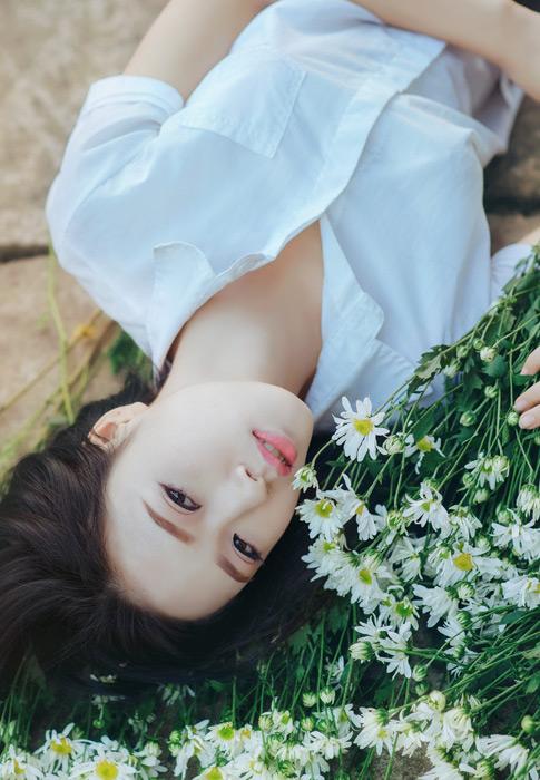 フリー写真 白い花と寝転ぶ女子学生のポートレイト