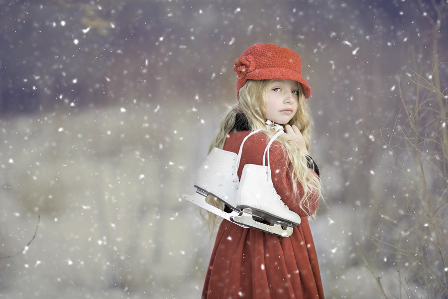 フリー写真 雪の中でスケート靴を背負う外国の女の子