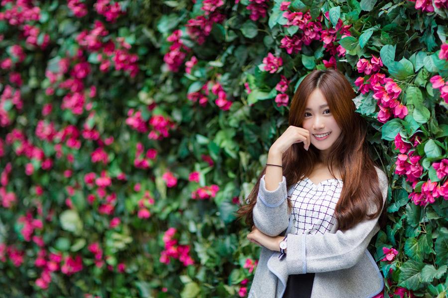 フリー写真 花の壁の前で頬杖をつく女性