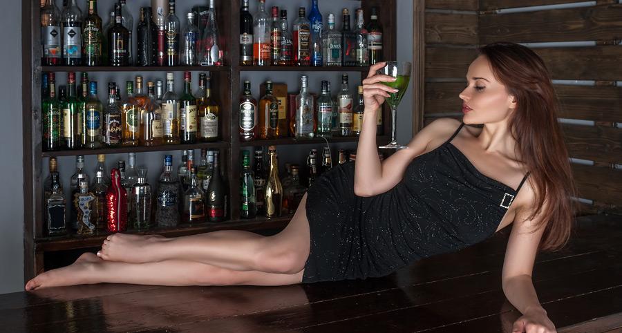 フリー写真 カクテルを持ってバーカウンターの上に横たわるロシア人女性