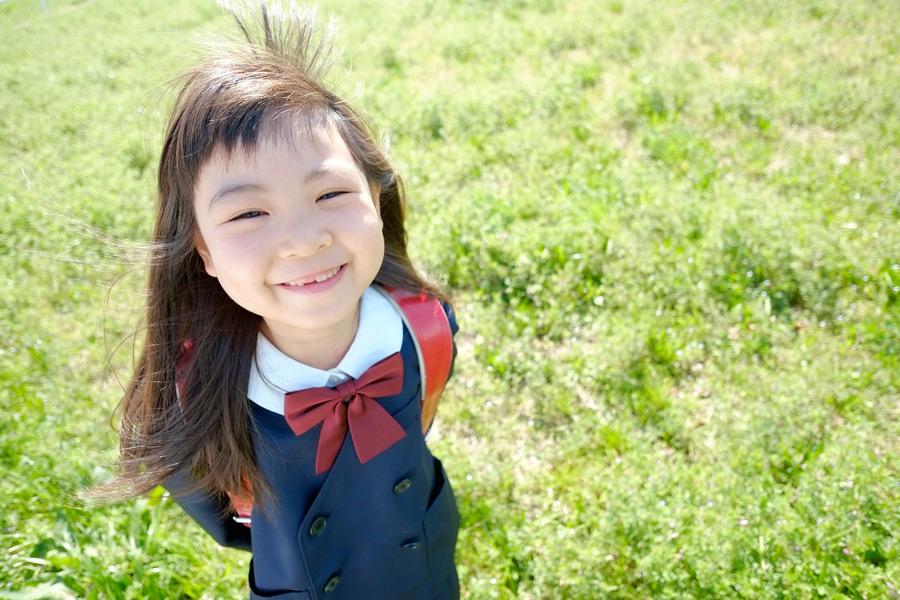 フリー写真 草むらで微笑む小学生の女の子