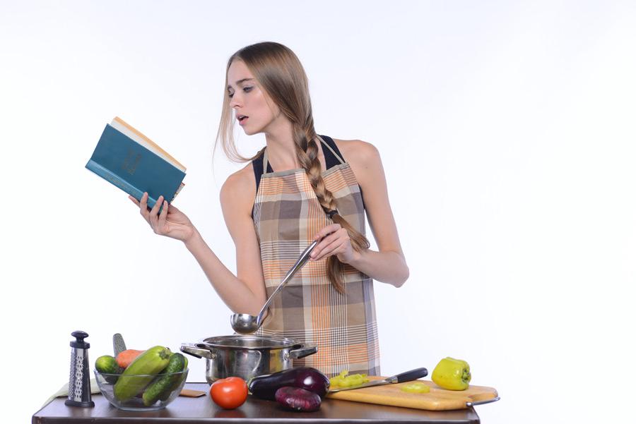 フリー写真 料理本を見ながら調理中の外国人女性