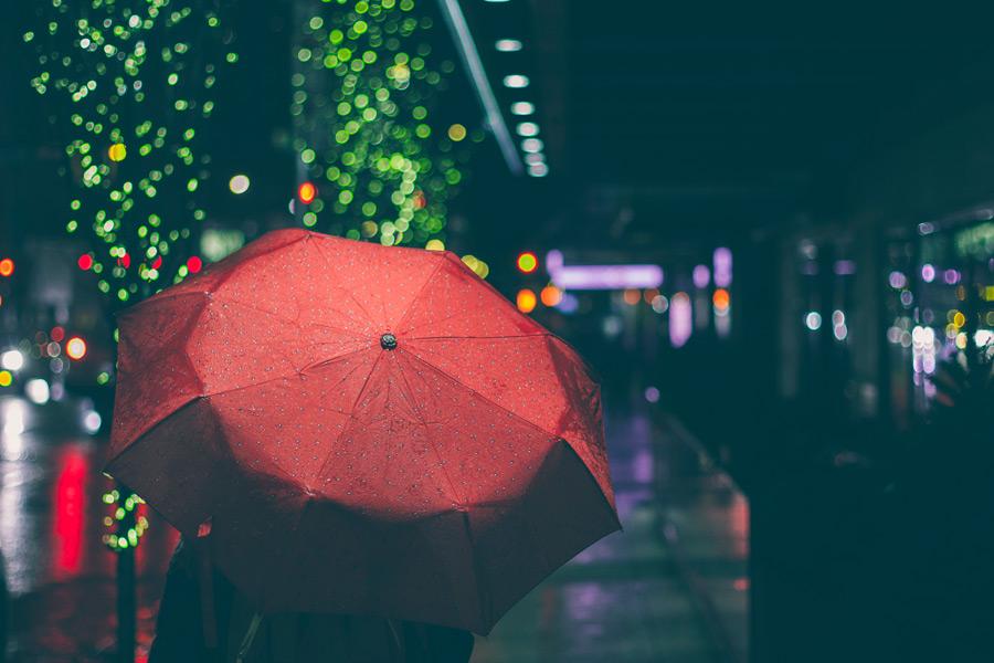フリー写真 傘を差して歩く人物とネオンの灯り