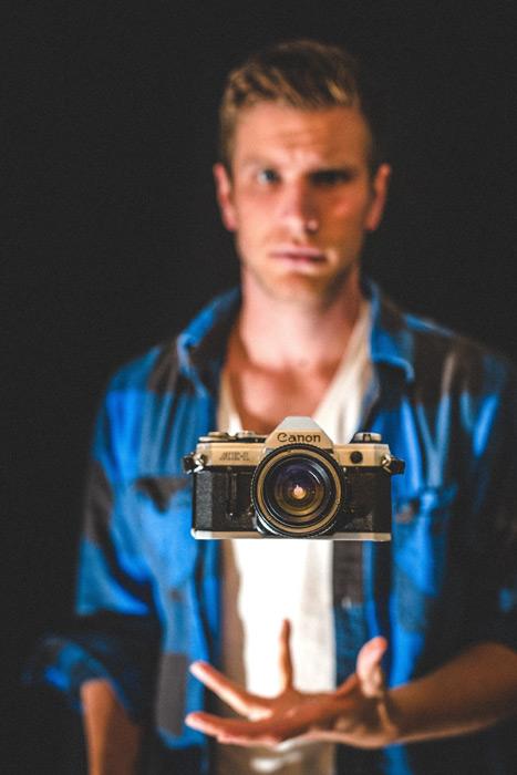 フリー写真 外国人男性と宙に浮かぶカメラ