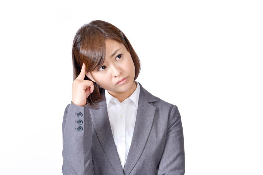 フリー写真 こめかみに指を当てながら悩む女性社員