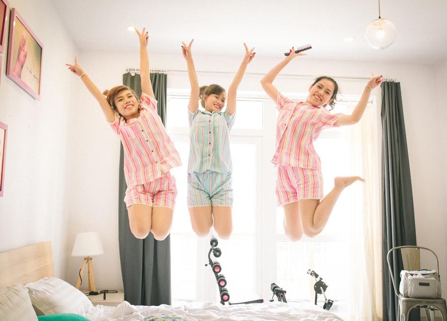 フリー写真 ベッドの上でジャンプする三人の女友達