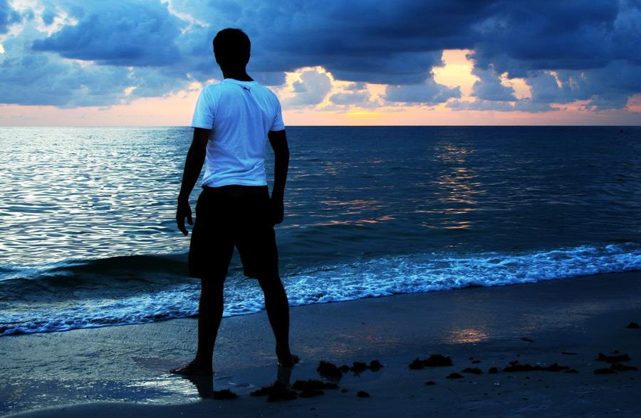 フリー写真 砂浜に立つ男性の後ろ姿