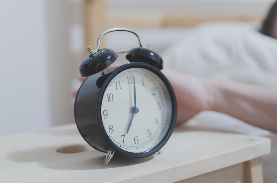 フリー写真 目覚まし時計と伸ばした手