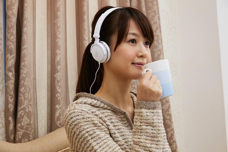 フリー写真 ヘッドホンをかけながら飲み物を飲む日本人女性