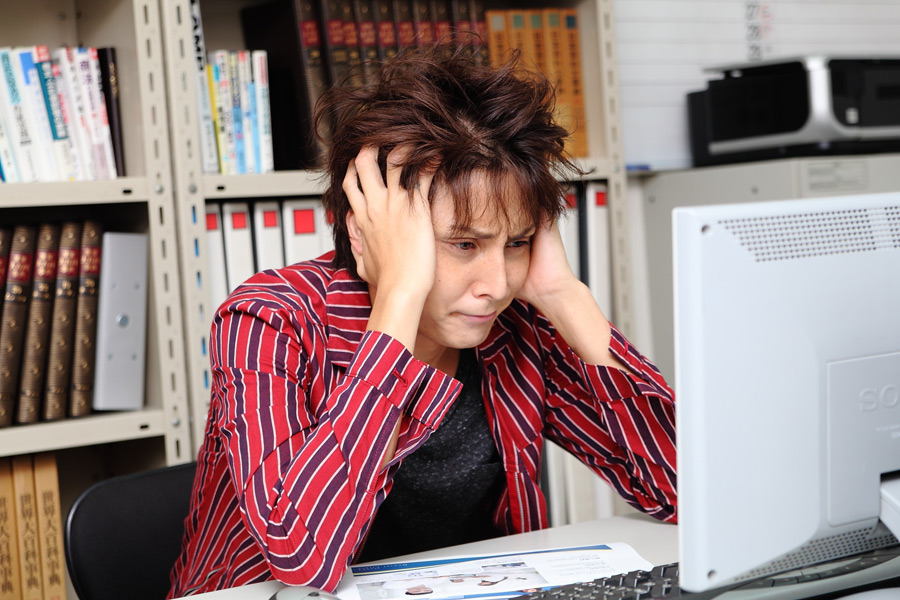 フリー写真 パソコンの前で頭を抱えるデザイナーの男性