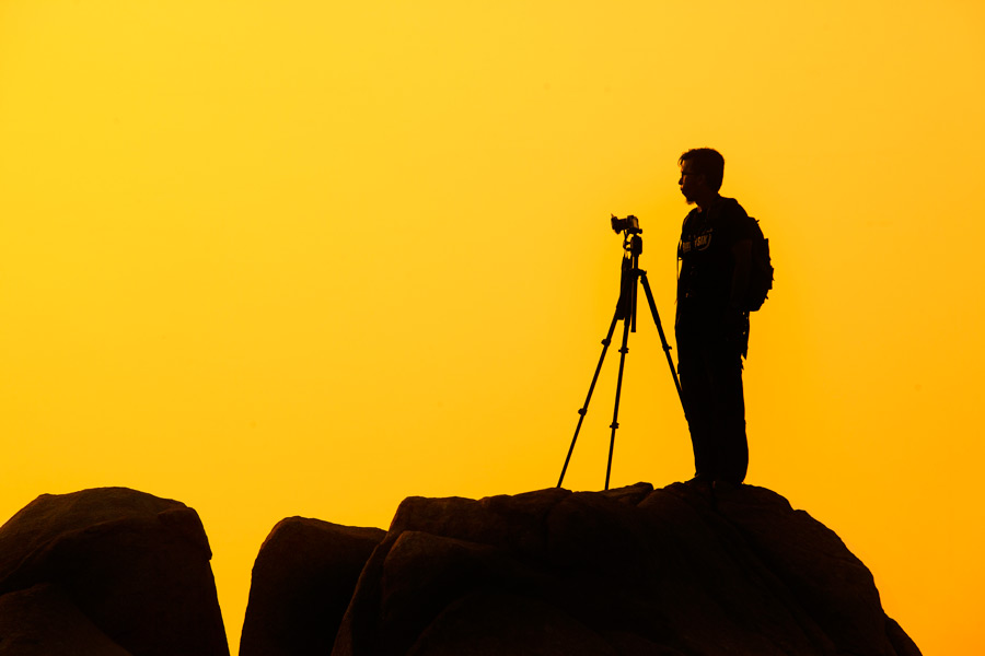 フリー写真 三脚を立ててシャッターチャンスを待つ男性