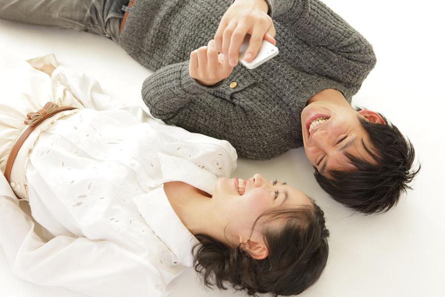フリー写真 寝転がってスマホを見て笑うカップル