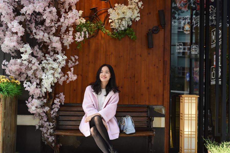 フリー写真 ベンチに足を組んで座る女性