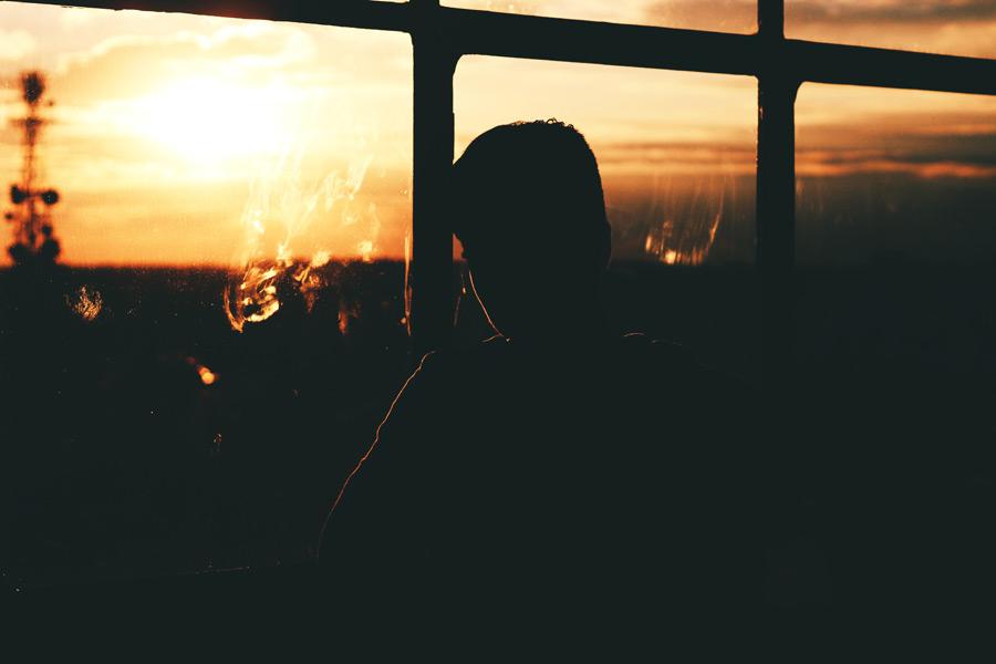 フリー写真 夕陽と窓辺の人物のシルエット