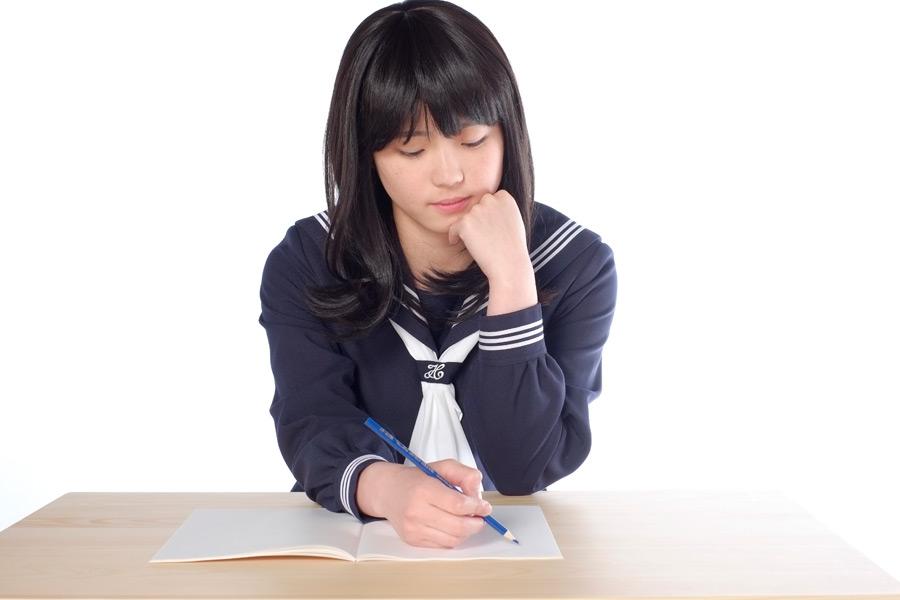 フリー写真 顎に手を当てながら勉強中の女子高生