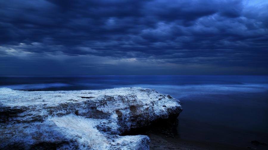 フリー写真 暗雲と海岸の岩と海の風景
