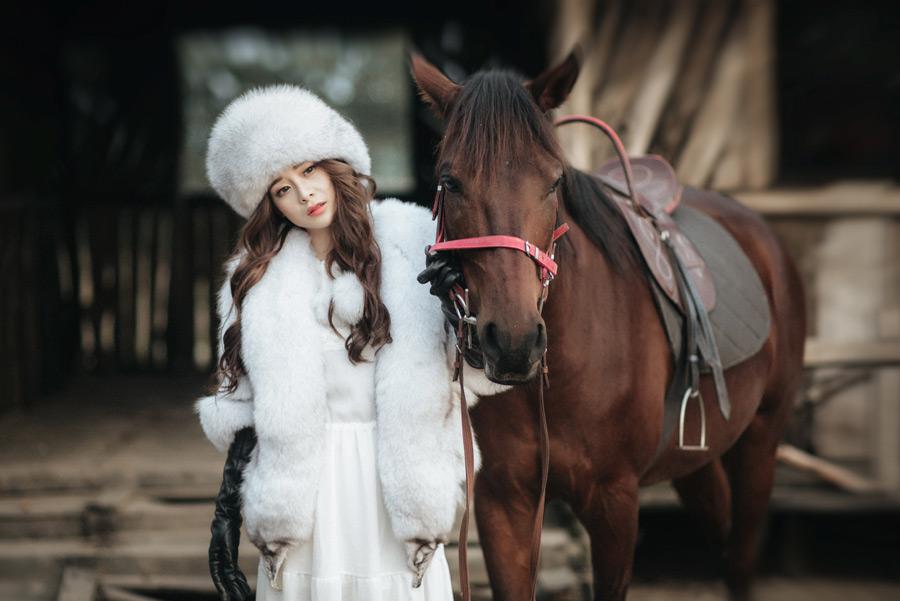 フリー写真 ロシア帽を被って馬を引く女性