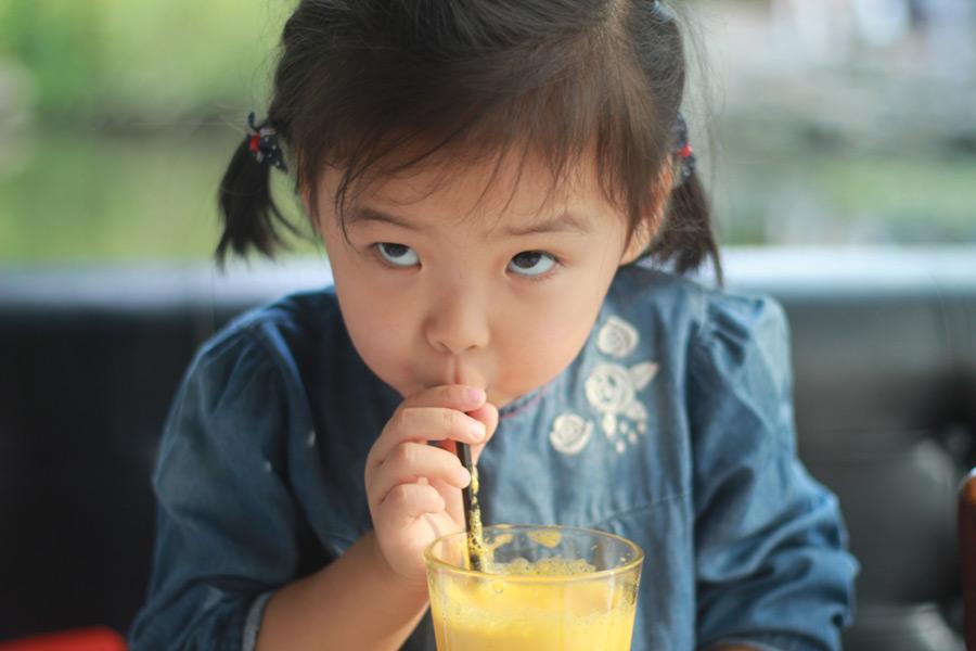 フリー写真 ストローでジュースを飲む女の子
