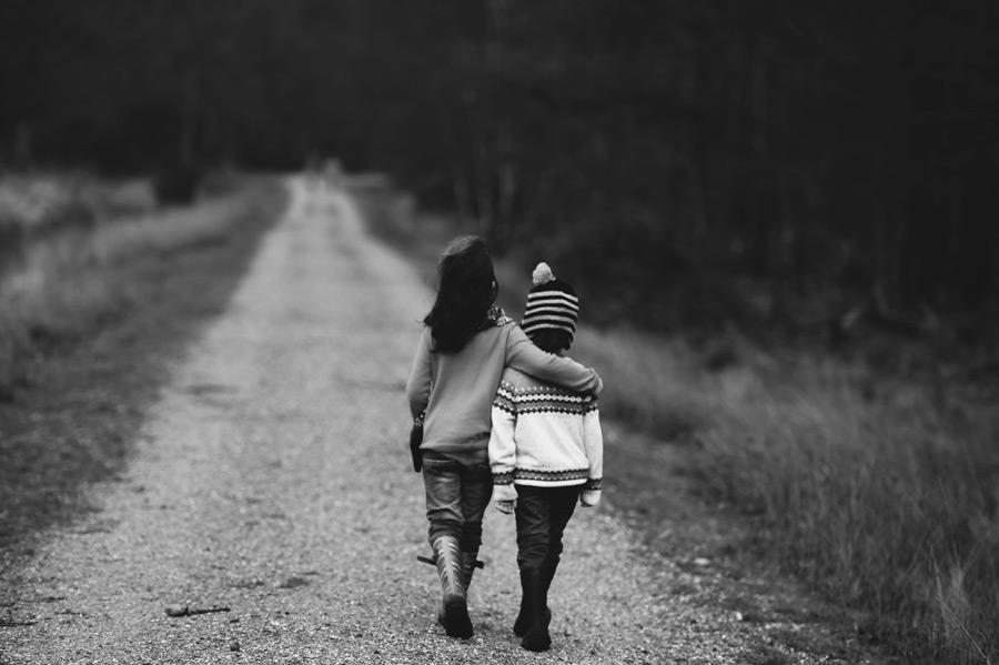 フリー写真 肩を組んで田舎道を歩く姉弟