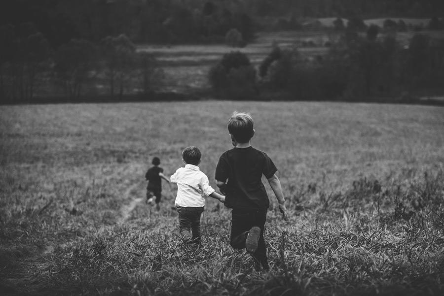 フリー写真 草むらを走る男の子たち
