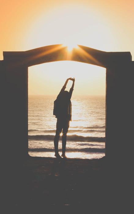 フリー写真 夕暮れの海と背伸びする女性