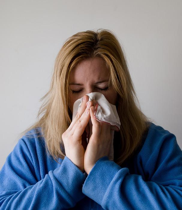 フリー写真 風邪をひいて鼻をかむ外国人女性