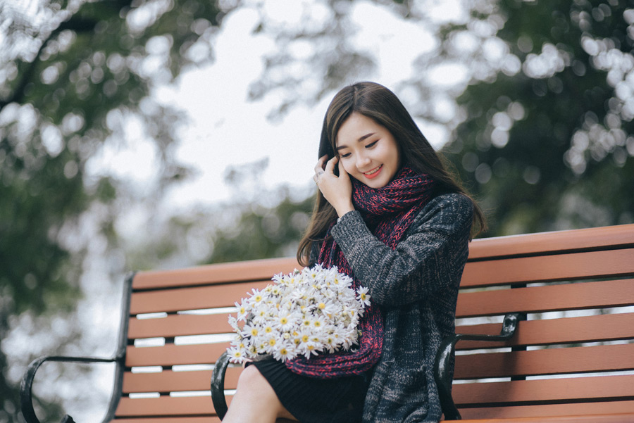 フリー写真 花束を膝の上に乗せてベンチに座る女性