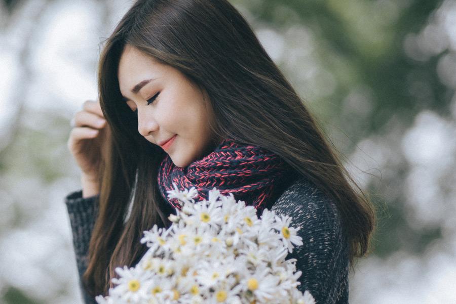フリー写真 花束を抱えて目を閉じる女性