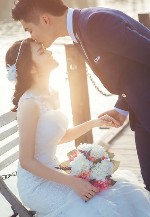 フリー写真 花嫁の額にキスをする花婿